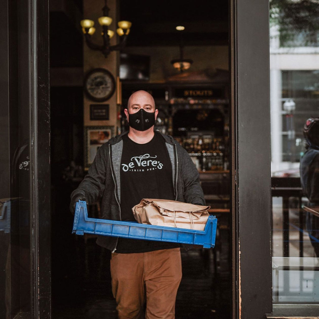 A restaurant worker in gloves and a mask is carrying a to-go order in a tray to prevent the spread of Covid-19.