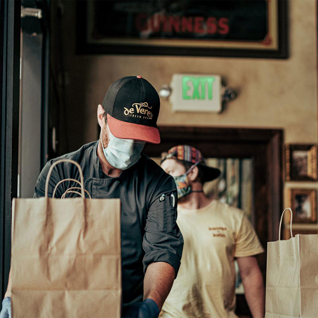 A restaurant worker is handling to-go orders in gloves and a mask to prevent the spread of Covid-19.