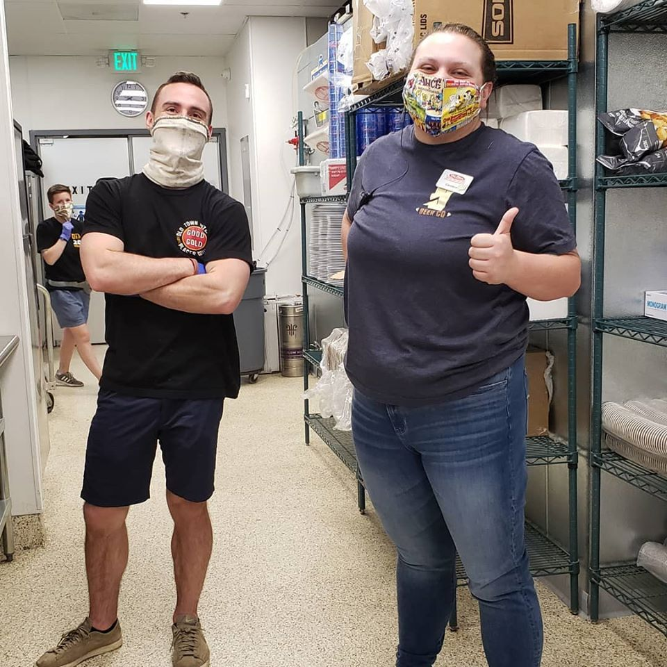 Old Town Pizza employees standing in the kitchen wearing masks to prevent the spread of Covid-19.