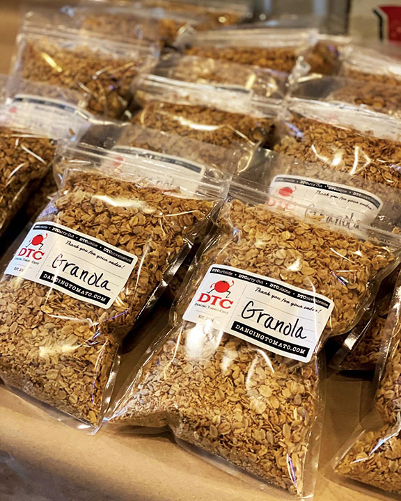 Bags of Granola sitting on a counter.
