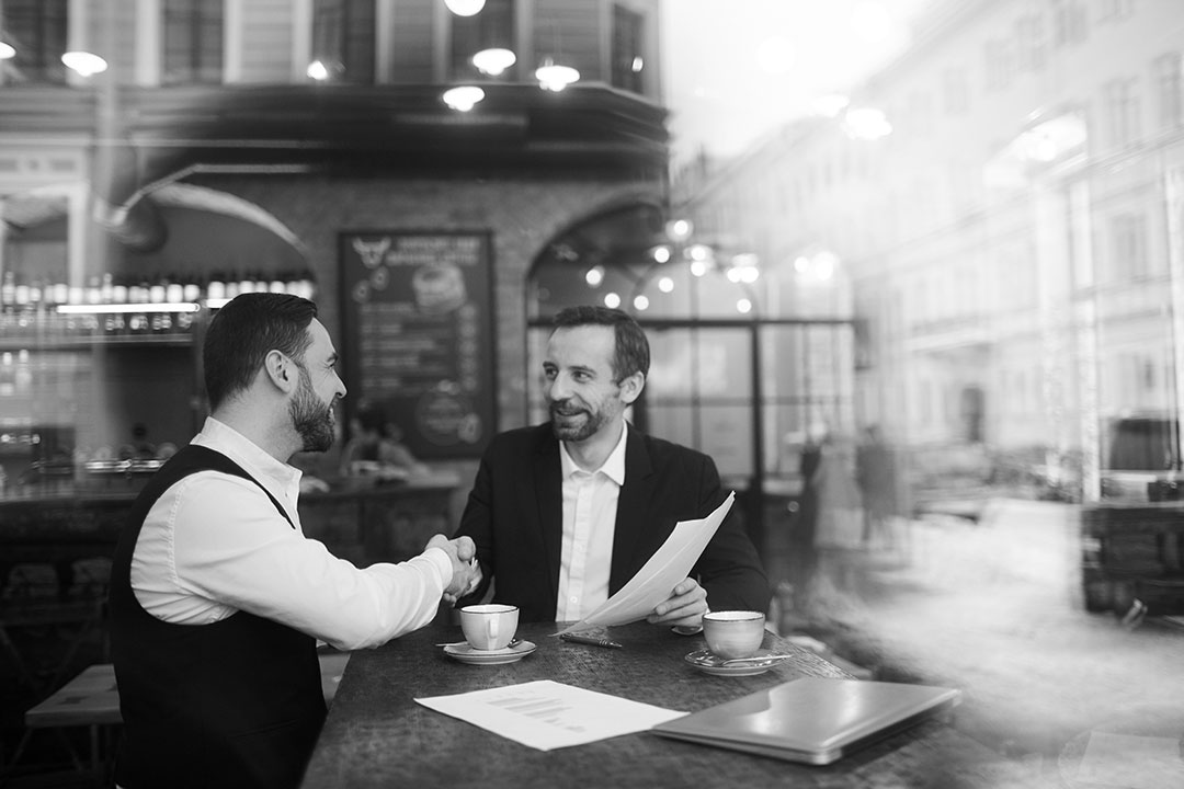 Two business people are shaking hands in a restaurant.